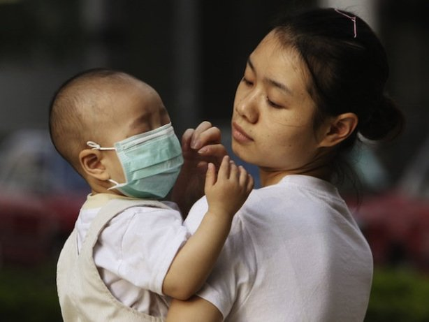 A baby in China wears a protective face mask (AP/Kin Cheung)